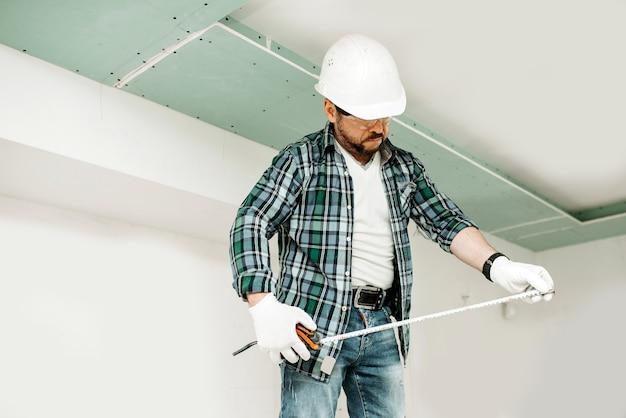 Een bouwer in een veiligheidshelm kijkt naar een meetlint tijdens het installeren van gipsplaat