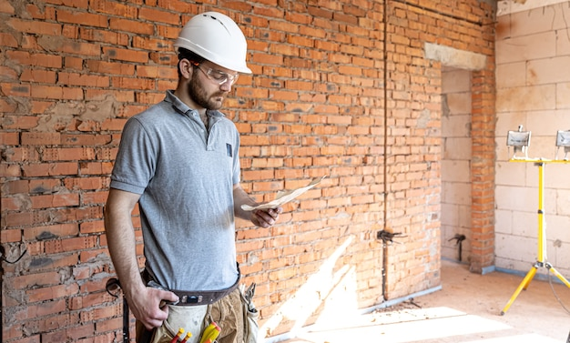Een bouwer in werkkleding onderzoekt een bouwtekening op een bouwplaats.