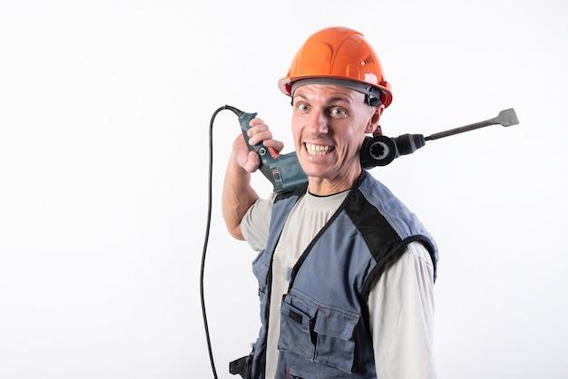 Een bouwer met een grappige uitdrukking, in een helm, met een boor op zijn schouder. voor elk doel.