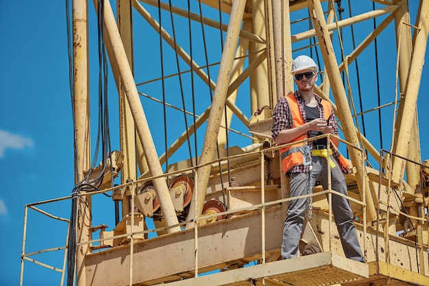 Een bouwingenieur in een geruit overhemd, een oranje vest en een witte helm op een gele bouwkraan met een portofoon in zijn handen. voorman, opzichter, arbeider