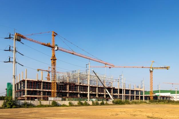 Een bouwplaats met verschillende kranen die aan een gebouw werken, boomkraan op de bouw van een hoogbouw en steigers in het gebouw, met blauwe lucht
