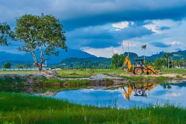 Een bouwtrekker werkt in een veld op een tropisch eiland