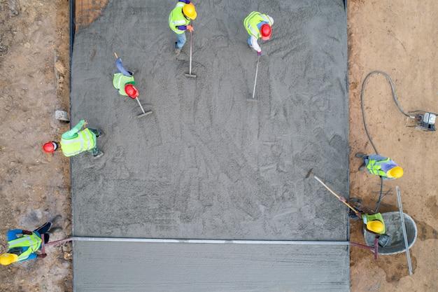 Een bouwvakker die een natte concret giet bij wegenbouwplaats