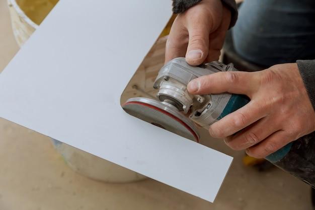 Een bouwvakker die een tegel snijdt die molen gebruikt
