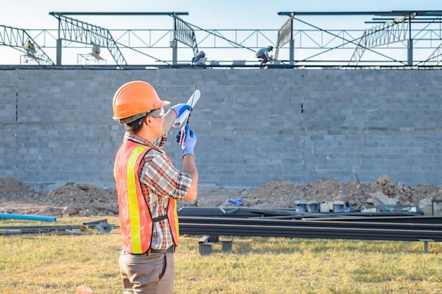 Een bouwvakker die momenteel werknemers bestelt sitegebied met radiocommunicatie