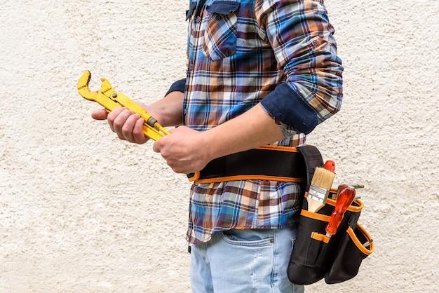 Een bouwvakker in een blauw geruit overhemd met gereedschap in zijn riem heeft een gele moersleutel in zijn handen.