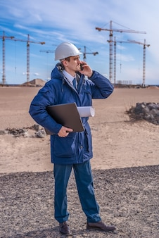 Een bouwvakker in een witte helm met een laptop en documenten onder zijn arm