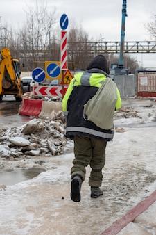 Een bouwvakker met een tas loopt in de winter langs de weg. achteraanzicht, groene jas, wegreparaties