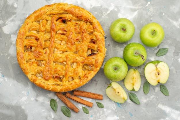 Een bovenaanzicht appeltaart ronde gevormd heerlijk met verse appels meel op de witte achtergrond cakekoekje