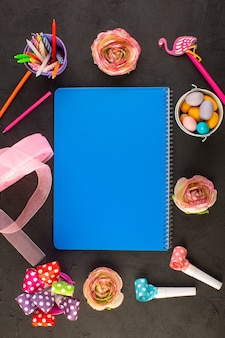 Een bovenaanzicht blauw voorbeeldenboek met bloemen snoepjes potloden rondom op het donkere bureau kleur snoep fotoboek