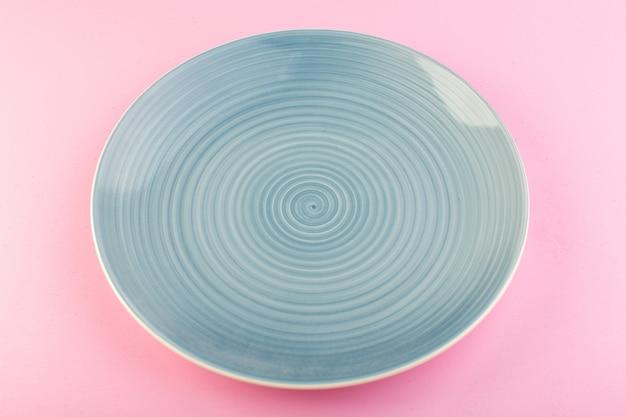 Een bovenaanzicht blauwe lege plaat glas gemaakt plaat voor maaltijd op roze