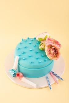 Een bovenaanzicht blauwe verjaardagstaart met bloem bovenop en kleurrijke kaarsen