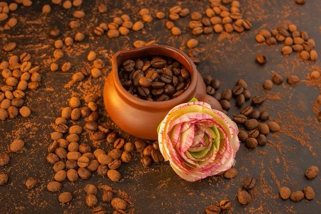 Een bovenaanzicht bruine koffiezaden in bruine kruik met bloem en overal op de bruine tafel