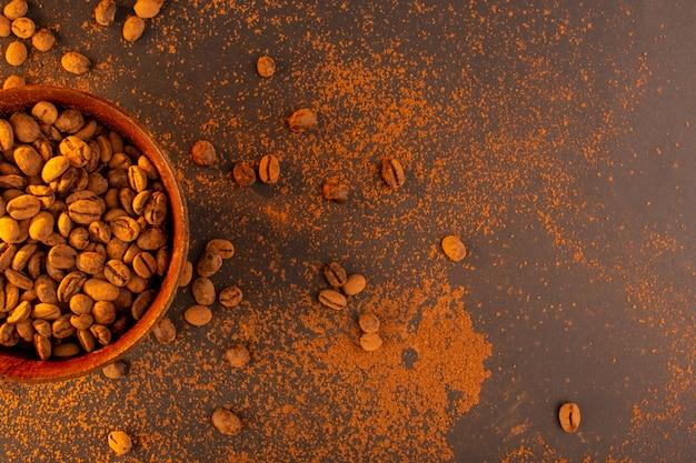 Een bovenaanzicht bruine koffiezaden in bruine plaat op de bruine achtergrond
