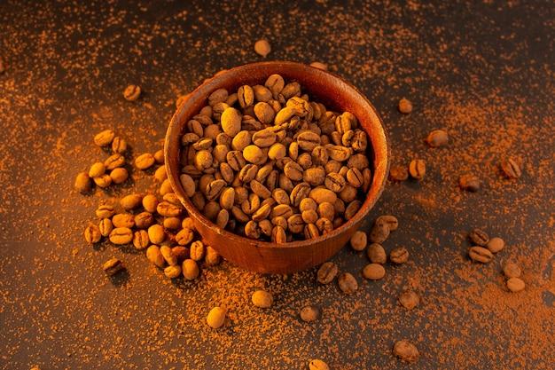 Een bovenaanzicht bruine koffiezaden in bruine plaat op de bruine tafel