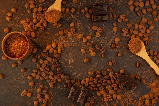 Een bovenaanzicht bruine koffiezaden met chocostaven helemaal over de bruine korrel van de achtergrondkoffiezaadkorrel