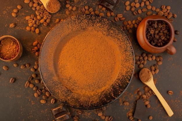 Een bovenaanzicht bruine koffiezaden samen met een zwarte plaat vol koffiepoeder met choco-repen over de bruine achtergrond