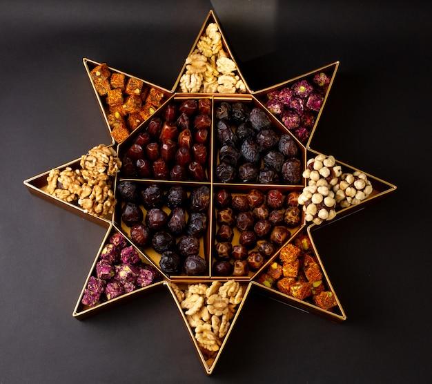 Een bovenaanzicht bureau met noten en verschillende gedroogde vruchten op het donkere oppervlak