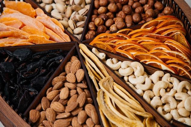 Een bovenaanzicht bureau met noten, walnoten, hazelnoten en amandelen binnen gevormd bureau op de witte noten walnoot gezouten snack
