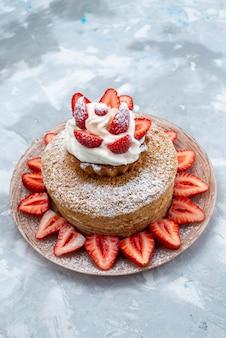 Een bovenaanzicht cakeplak met room en verse rode aardbeien binnen plaat op het blauwgrijze cakefruit als achtergrond