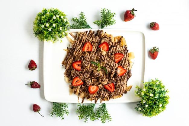 Een bovenaanzicht choco aardbei dessert lekker zoet samen met hele aardbeien en planten verspreid over de witte achtergrond fruitcake