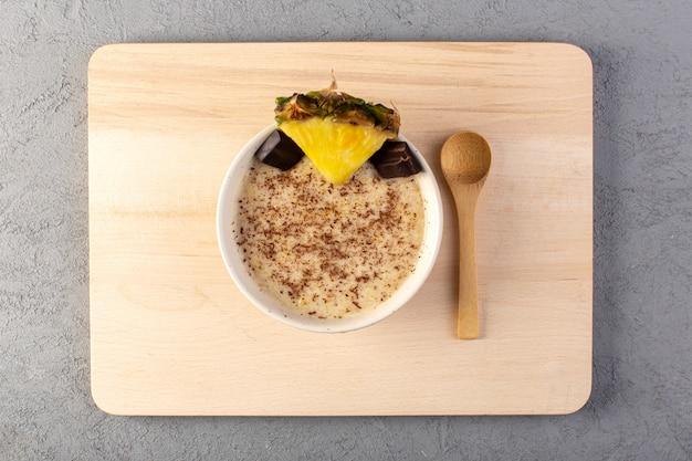 Een bovenaanzicht choco dessert bruin met ananas segment choco repen op het crème houten bureau en grijs
