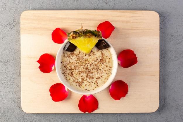 Een bovenaanzicht choco dessert bruin met ananasschaaf choco bars rode roos en bloemblaadjes op het crème houten bureau en grijs
