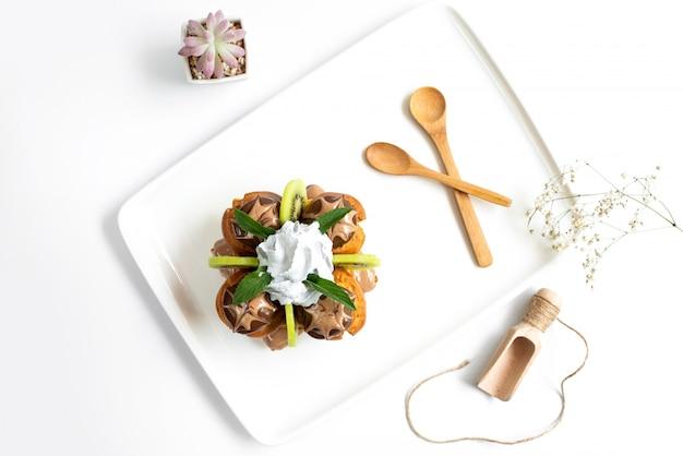 Een bovenaanzicht choco-dessert samen met gesneden kiwi's en vla in een wit bureau samen met houten lepels op de witte achtergrond cake-ijs zoet
