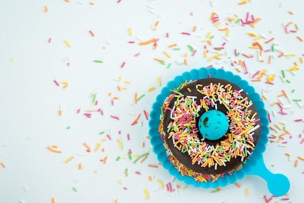 Een bovenaanzicht chocolade donut met kleine kleurrijke snoepjes op wit bureau, snoep kleur snoepjes