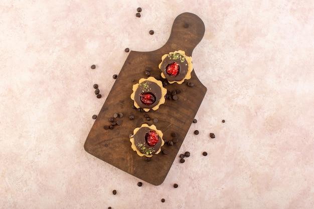 Een bovenaanzicht chocoladecake op het houten bureau en de roze tafel