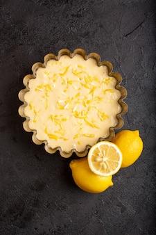 Een bovenaanzicht citroentaart zure heerlijke exotische bakkerij taart zoet met verse citroenen op het donkere bureau