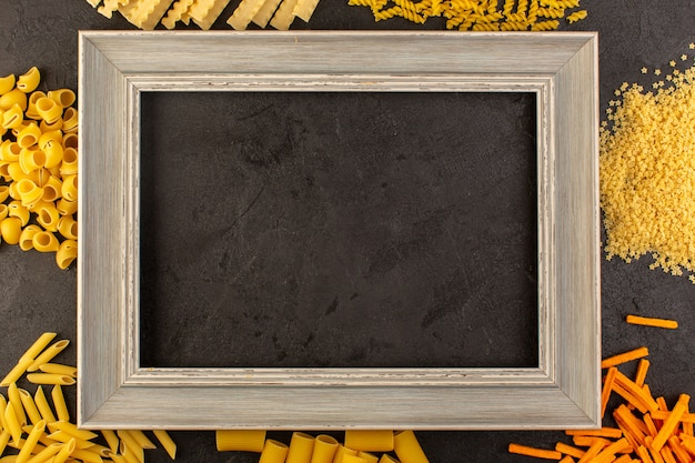 Een bovenaanzicht donkere fotolijst samen met verschillende gevormde gele rauwe pasta geïsoleerd in het donker