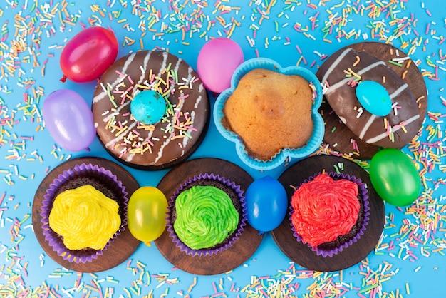 Een bovenaanzicht donuts en brownies heerlijk en chocolade gebaseerd, samen met snoepjes op blauw, candy cake biscuit kleur