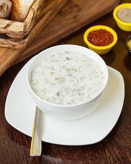 Een bovenaanzicht dovga met greens binnen witte plaat op de bruine houten maaltijd van de de soepyoghurt van het bureauvoedsel
