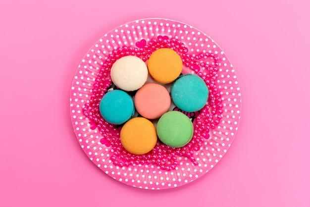 Een bovenaanzicht franse macarons kleurrijke ronde heerlijk binnen roze, plaat op roze, cake biscuit banketbakkerij