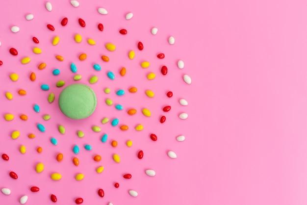 Een bovenaanzicht franse macarons met kleurrijke snoepjes op roze, suiker cake biscuit kleur samenstelling regenboog