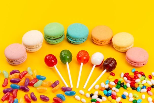 Een bovenaanzicht franse macarons samen met lollies en kleurrijke snoepjes verspreid over gele, suikerzoete banketbakkerij