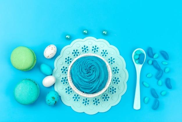 Een bovenaanzicht franse macarons samen met schuimgebakjes en lepels op blauwe, zoete cakekleur