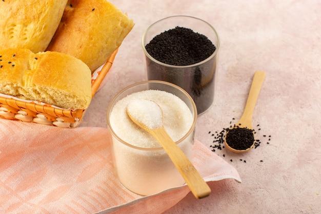 Een bovenaanzicht gebakken brood warm lekker vers gesneden in broodtrommel samen met zout en peper op roze