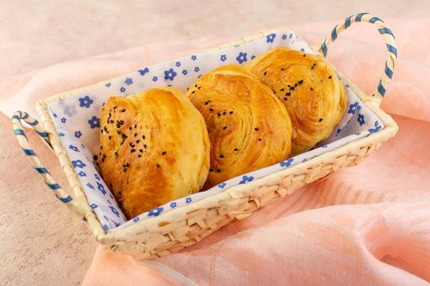 Een bovenaanzicht gebakken broodjes warm lekker vers in broodtrommel op roze