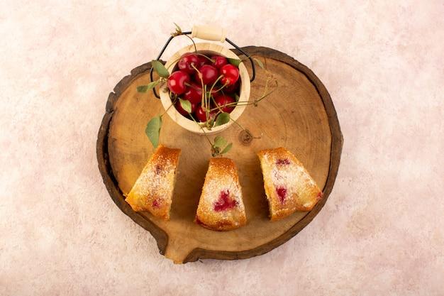 Een bovenaanzicht gebakken fruitcake heerlijk gesneden met rode kersen binnen en suikerpoeder op houten bureau met verse kersen op roze