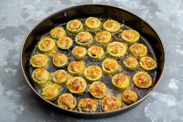 Een bovenaanzicht gebakken pompoen ringen in grote zwarte pan gezouten en smakelijk op het lichte bureau gekookt groente maaltijd eten