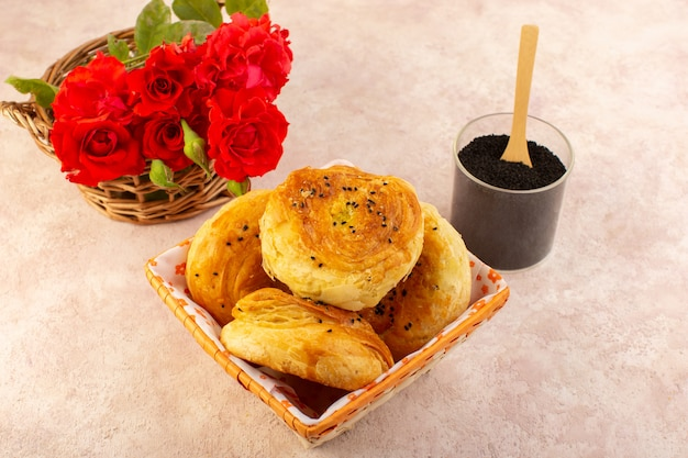 Een bovenaanzicht gebakken qogals oost-gebakken broodjes vers warm in broodtrommel samen met rode bloemen en peper op tafel en roze