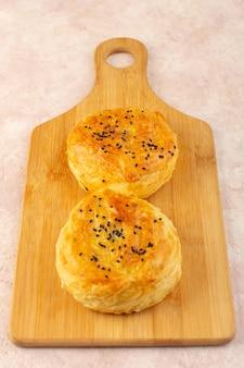 Een bovenaanzicht gebakken qogals rond gevormd lekker warm vers uit de oven op het bruine houten bureau