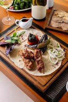 Een bovenaanzicht gebakken vlees botten met gebakken groenten en saus op tafel eten maaltijd diner restaurant vlees