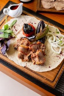 Een bovenaanzicht gebakken vlees botten met gebakken groenten en saus op tafel eten maaltijd diner restaurant
