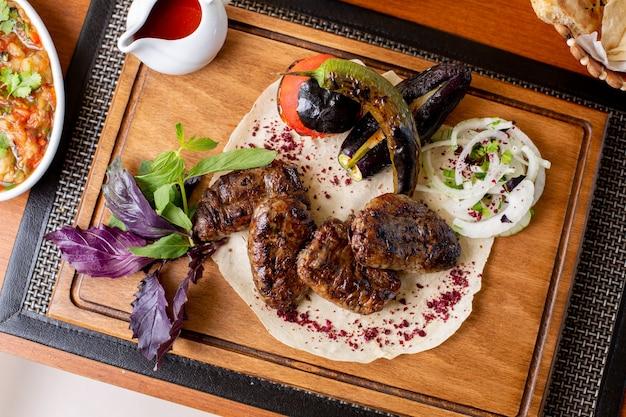 Een bovenaanzicht gebakken vlees met saus, verse groenten en wijn op tafel eten maaltijd vlees restaurant