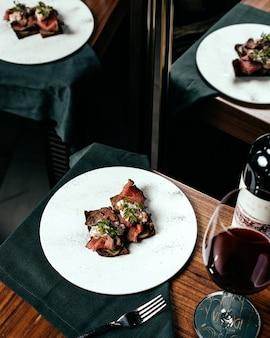Een bovenaanzicht gebakken vleesgerecht met glas wijn op tafel vleesmaaltijd eten
