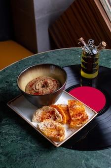 Een bovenaanzicht gekookt gerecht in plaat en dienblad op het groene tafelvoedselmaaltijdrestaurant