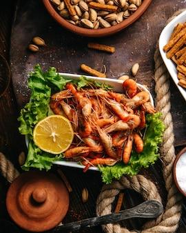 Een bovenaanzicht gekookte garnalen met groene salade en citroen op de houten de maaltijd zeevruchten van het lijstvoedsel